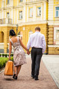 Couple walking away women with heavy case Royalty Free Stock Photo