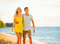 Couple walking on the beach at sunset romantic vacation attractive happy Stock Images