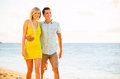 Couple walking on the beach at sunset romantic vacation attractive happy Royalty Free Stock Photo