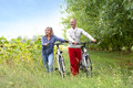 Couple walking with bicycle in hands cheerful senior country path Royalty Free Stock Photos