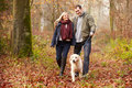 Couple walking dog through winter woodland happy wearing warm clothing Stock Photography