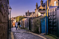 Couple walking down cobblestone street a a in an old town Stock Photos