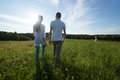Couple walking through field young green Royalty Free Stock Images
