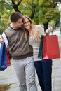 Couple walking leisurely on sidewalk happy young together with shopping bags Stock Image