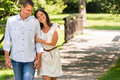 Couple walking in park hand in hand smiling a Stock Photography