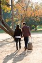Couple walking in park with traveling trolley. Stock Photos