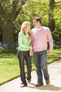 Couple walking on path holding hands smiling Royalty Free Stock Photos