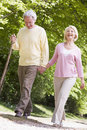 Couple walking on path in park holding hands Royalty Free Stock Image