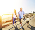 Couple walking pet dog by the ocean photo of a Royalty Free Stock Images