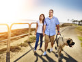 Couple walking pet dog by the ocean photo of a with motion blur Stock Photos