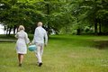 Couple walking with portable barbecue rear view of a in casual clothing walks a barbeque in forest park Royalty Free Stock Photography