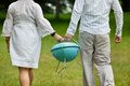 Couple walking with portable barbeque back view of a in casual wear a on an outdoor picnic Royalty Free Stock Images