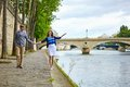 Couple is walking by the seine embankment in paris Stock Photos