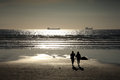 Couple walking on a silhouette sunset beach Royalty Free Stock Photo