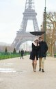 Couple walking under the rain with broken umbrella paris france Royalty Free Stock Photo