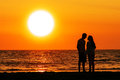 Couple walking under the sunset silhouette of a at beach of scheveningen netherlands Stock Photography