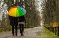 Couple walks under rainbow umbrella
