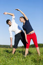 Couple warming up for exercise in summer Royalty Free Stock Images