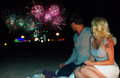 Couple watching colorful fireworks at the beach young Stock Image