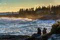 Couple watching large waves crash on rocks at sunset, at Pemaqui Royalty Free Stock Photo