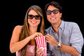Couple watching movie in d isolated over a black background Royalty Free Stock Images