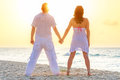 Couple watching romantic sunrise beach Stock Photo