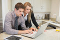 Couple watching something on the laptop in kitchen Stock Photography