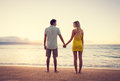 Couple watching the sunset happy romantic holding hands on tropical beach vacation vintage trendy color styling Stock Images