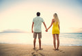 Couple watching the sunset happy romantic holding hands on tropical beach vacation vintage trendy color styling Royalty Free Stock Photography