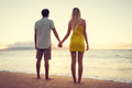 Couple watching the sunset happy romantic holding hands on tropical beach vacation vintage trendy color styling Royalty Free Stock Image