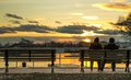 Couple watching the sunset lovers looking at sitting on a bench Royalty Free Stock Photo
