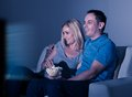 Couple watching television and eating popcorn at home happy Royalty Free Stock Image