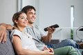 Couple watching television happy young together at home Stock Image