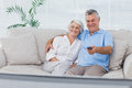 Couple watching television sitting on the couch mature Stock Photos
