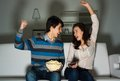 Couple watching tv on the couch sports fans Royalty Free Stock Photos