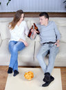 Couple watching tv relaxed young and drinking beer at home in bright living room Royalty Free Stock Image
