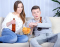Couple watching tv relaxed young and drinking beer at home in bright living room Royalty Free Stock Photo