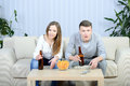 Couple watching tv relaxed young and drinking beer at home in bright living room Stock Images