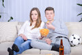 Couple watching tv relaxed young and drinking beer at home in bright living room Royalty Free Stock Images