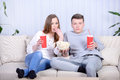 Couple watching tv relaxed young and drinking cola at home in bright living room Royalty Free Stock Photo
