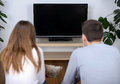Couple watching tv relaxed young at home in bright living room Royalty Free Stock Photography
