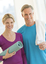 Couple with water bottle exercise mat and towel in gym portrait of happy Royalty Free Stock Photo