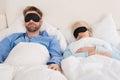 Couple Wearing Eyemask While Sleeping On Bed Royalty Free Stock Photo