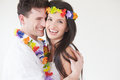 Couple wearing flower garlands against white background smiling Stock Image