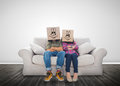 Couple wearing funny boxes on their head a couch Stock Photos