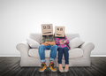 Couple wearing humorous boxes on their head a couch Royalty Free Stock Photos