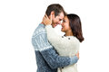 Couple wearing warm clothing embracing against white background Stock Photography