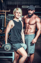 Couple of well trained bodybuilder with dumbbells in club Stock Photos
