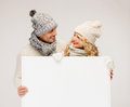 Couple in winter clothes with blank white board christmas x mas people advertisement sale concept happy women and men Royalty Free Stock Photos
