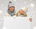 Couple in a winter clothes holding blank board picture of family Royalty Free Stock Photography